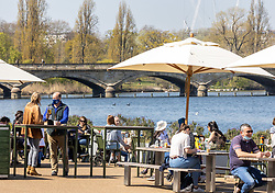 Licensed to London News Pictures. 19/04/2021. London, UK. Members of the public enjoy a pint next to the Serpentine and soak up the sunshine in Hyde Park, London a week after the easing of Covid-19 restrictions as a mini heatwave hit the UK this week with temperatures reaching up to 18c in London and the South East. Photo credit: Alex Lentati/LNP
