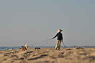 Early morning on a part of China beach in Danang. A woman wearing a traditional Vietnamese hat is walking on the beach while keeping her three dogs on a leash.