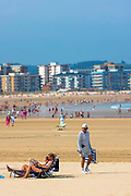 Beach scene and people sunbathing on summer holiday in Laredo, Cantabria, Spain