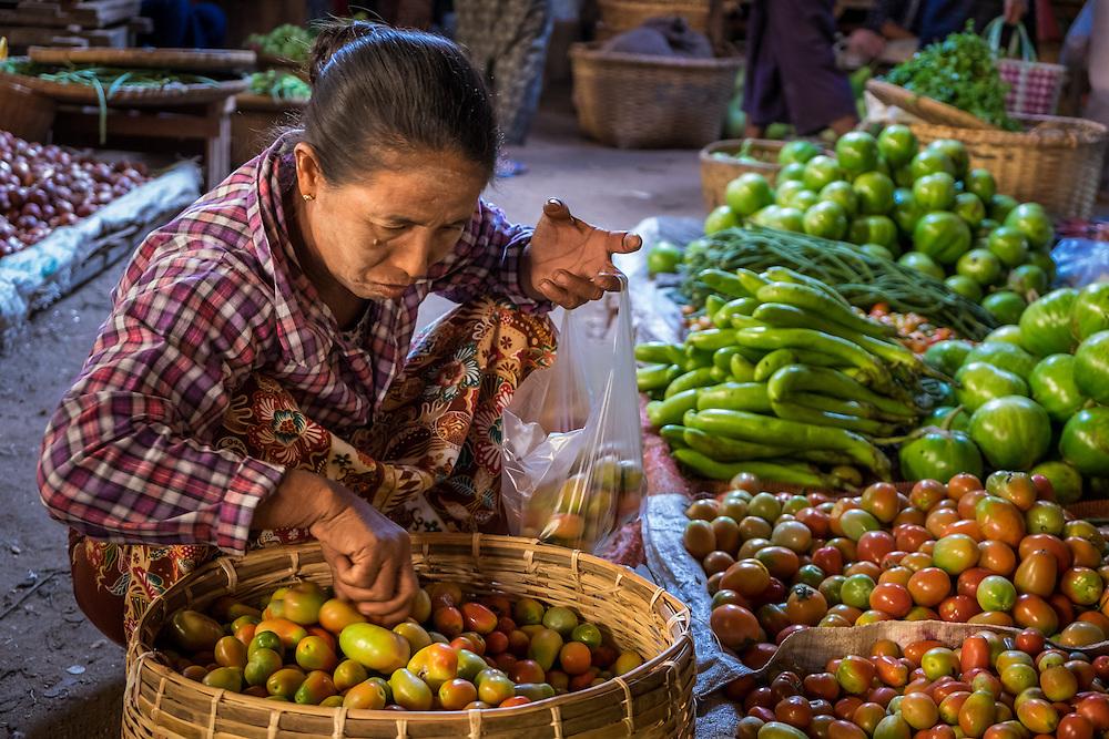 BAGAN, MYANMAR - CIRCA DECEMBER 2013: Burmese woman buying vegetables in the Nyaung U market close to Bagan in Myanmar