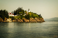Owls Head Lighthouse at sunset on a beautiful summer evening, taken from a boat off the coast. Sailboat in the distance along wiht hazy hills all add interest to the scene.