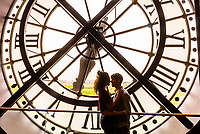 """Lovers embrace in front of the clock at Musee d""""Orsay,  a museum in Paris, France, on the Left Bank of the Seine. It is housed in the former Gare d'Orsay, a Beaux-Arts railway station built between 1898 and 1900."""
