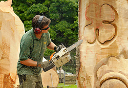 "© Licensed to London News Pictures. 25/08/2012. Westonbirt, Tetbury, Gloucestershire, UK. Carver David Lucas makes ""Knock on Wood"", a muscial sculpture with hollowed out chambers at Treefest in Westonbirt Arboretum.  Treefest runs till 27 August.  25 August 2012..Photo credit : Simon Chapman/LNP"