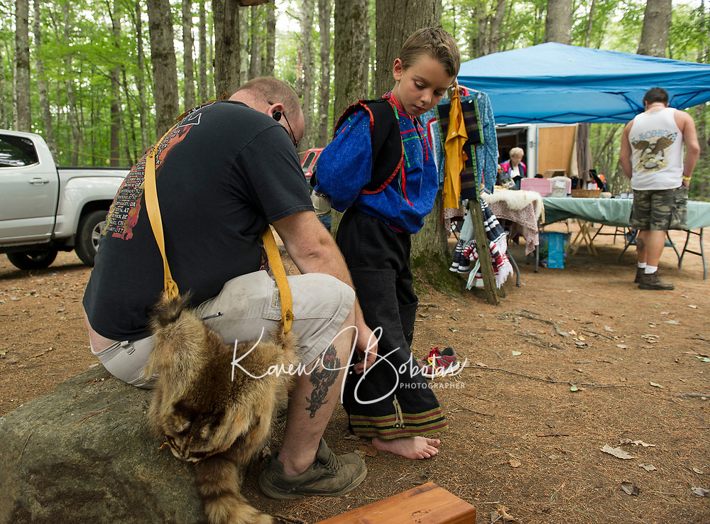 Charles Marriner lends a hand to Joshua Elder as they put on Elder's regalia for the Grand Entry and tribal dances during the 48th annual LIHA Labor Day Pow Wow in Sanbornton.  (Karen Bobotas/for the Laconia Daily Sun)