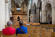 Two men sit on a pew in Rochester Cathedral, on 22nd July, in Rochester, England.