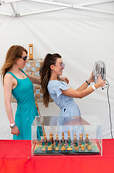 © Licensed to London News Pictures. 18/07/2021. LONDON, UK. Staff members on a stall selling chessboards at Chess Fest in Trafalgar Square keep cool as temperatures are expected to exceed 30C today.  The event celebrates the game of chess and visitors can learn the game, play chess or challenge a Grandmaster.  Also, to celebrate the 150th anniversary of Lewis Carroll's Alice Through the Looking Glass book which featured the game of the chess, 32 actors dressed as Alice Through the Looking Glass characters stand on a giant chessboard replaying a game based on the book.  Photo credit: Stephen Chung/LNP