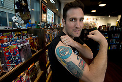 Eitan Manhoff, owner of Cape & Cowl Comics in the Uptown neighborhood of Oakland, Calif., shows off some of the superhero tattoos on his biceps, as he poses for a photograph his shop, Tuesday, Nov. 24, 2015. (D. Ross Cameron/Bay Area News Group)