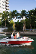 A family in a motor launch going along one of the canals in Miami Beach