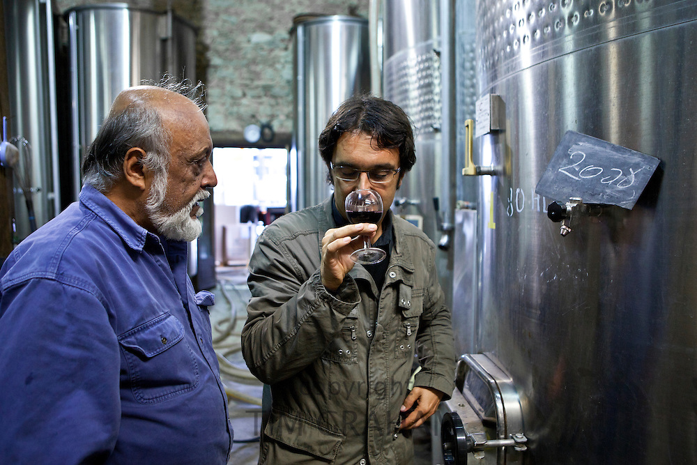 Oenologist sniffs the 2008 vintage watched by proprietor at Chateau Fontcaille Bellevue, Bordeaux wine region of France