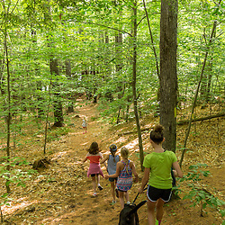 Girls walking a dog on a trail near Page Pond in Meredith, New Hampshire.