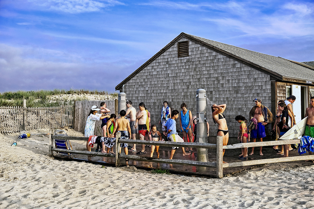 Vacationers wash off sand in outdoor beach showers, Nauset Beach, Cape Cod, MA, USA