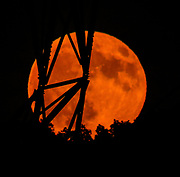 The red moon shines through the cables of the electric tower.