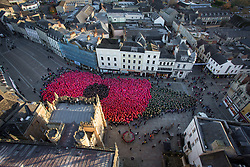 """**2018 Pictures of the year by London News Pictures**<br /> © Licensed to London News Pictures 11/11/2018, Cirencester, UK. People gather to form a world record breaking (pending conformation) """"human poppy"""" in Cirencester town Market Place to commemorate the end of the First World War 100 years ago today. Over 3,300 people wore coloured ponchos to create the shape of a poppy and leaf. Photo Credit : Stephen Shepherd/LNP"""