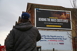 © Licensed to London News Pictures. 21/02/2021. London, UK. A man walks past the government's 'Bending The Rules Costs Lives' awareness publicity campaign poster displayed on the side of a property in north London. Prime Minister Boris Johnson will announce on Monday, 22 February the government's plans for relaxing Covid-19 restrictions in England. It is expected that families to be reunited, and schools will re-open on 8 March. Photo credit: Dinendra Haria/LNP
