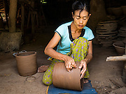 30 OCTOBER 2015 - TWANTE, MYANMAR: A woman works on a pot in a shed in the potters' village in Twante, (also spelled Twantay) Myanmar. Twante, about 20 miles from Yangon, is best known for its traditional pottery. The pottery makers are struggling to keep workers in their sheds though. As Myanmar opens up to outside investments and its economy expands, young people are moving to Yangon to take jobs in the better paying tourist industry or in the factories that are springing up around Yangon.     PHOTO BY JACK KURTZ