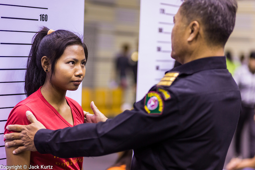 "17 JULY 2014 - BANGKOK, THAILAND: A Thai immigration police officer helps an undocumented Cambodian worker pose for a ""mug shot"" for a temporary ID card. at the temporary ""one stop service center"" in the Bangkok Youth Center in central Bangkok. Thai immigration officials have opened several temporary ""one stop service centers"" in Bangkok to register undocumented immigrants and issue them temporary ID cards and work permits. The temporary centers will be open until August 14.    PHOTO BY JACK KURTZ"