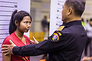 """17 JULY 2014 - BANGKOK, THAILAND: A Thai immigration police officer helps an undocumented Cambodian worker pose for a """"mug shot"""" for a temporary ID card. at the temporary """"one stop service center"""" in the Bangkok Youth Center in central Bangkok. Thai immigration officials have opened several temporary """"one stop service centers"""" in Bangkok to register undocumented immigrants and issue them temporary ID cards and work permits. The temporary centers will be open until August 14.    PHOTO BY JACK KURTZ"""