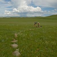 Nearby a summer thundershower, a Smithsonian Museum archaeology team studies a 2700+ year-old khirigsur burial mound at Ulaan Tolgoi, near Lake Erkhel & Muren, Mongolia.