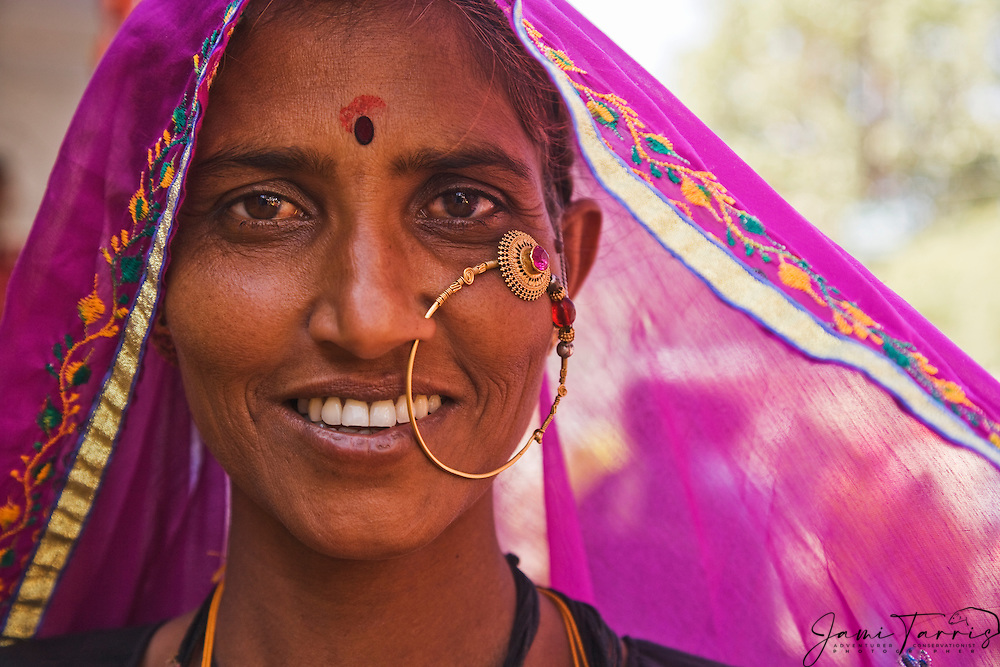 Portrait of a woman in a fuschia pink sari with  elaborate tribal jewelry and a big smile, Pushkar camel fair, Rajasthan, India