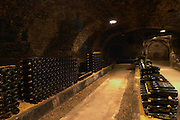 In the underground wine cellar: piles of thousands of bottles Burgundy wine on a gravelly pebbly soil vaulted vault ceiling with contrasting lights, Maison Louis Jadot, Beaune Côte Cote d Or Bourgogne Burgundy Burgundian France French Europe European
