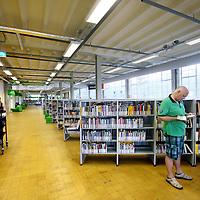 Nederland, Zaandam , 5 juli 2013.<br /> Wandeling door de binnenstad van  Zaandam. <br /> Starten bij De Werf aan de Oostzijde. Daarvandaan kun je lopen op een soort boulevard tussen de flats en het water. De eerste stop is De Fabriek, filmhuis en eetcafé met terras aan de Zaan met uitzicht op de sluis. Daarna de sluis zelf.<br /> Dan langs het winkelgebied richting de Koekfabriek: Het oude Verkade pand dat is verbouwd en waar nu de bieb en sportschool en restaurant etc. in zitten.<br /> (Dat is aan de overkant van het startpunt) en misschien nog de Zwaardemaker meepakken aan de Oostzijde. Dat is een oud pakhuis die Rochdale enige jaren geleden heeft verbouwt tot appartementen met een stukje Nieuwbouw.<br /> Ook doen: het Russische buurtje vlakbij de Zaan. Dit jaar staat Rusland in de schijnwerpers en Zaandam heeft een speciale band met Rusland, vanwege het Czaar Peterhuisje en de Russische buurt. <br /> Op de foto: De bibliotheek  de Bieb genaamd op de 1e etage in de Chocoladefabriek aan de Westzijde<br /> Foto:Jean-Pierre Jans