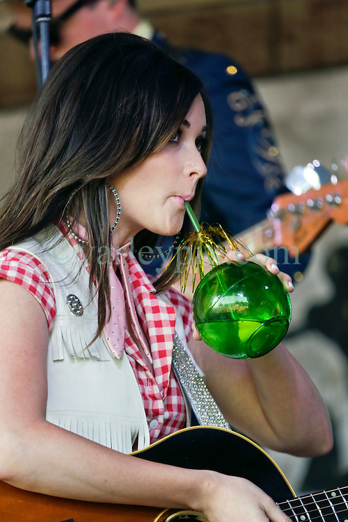03 May 2015. New Orleans, Louisiana.<br /> The New Orleans Jazz and Heritage Festival. <br /> Kacey Musgraves sips an unusual drink on the Fais Do-Do stage.<br /> Photo; Charlie Varley/varleypix.com