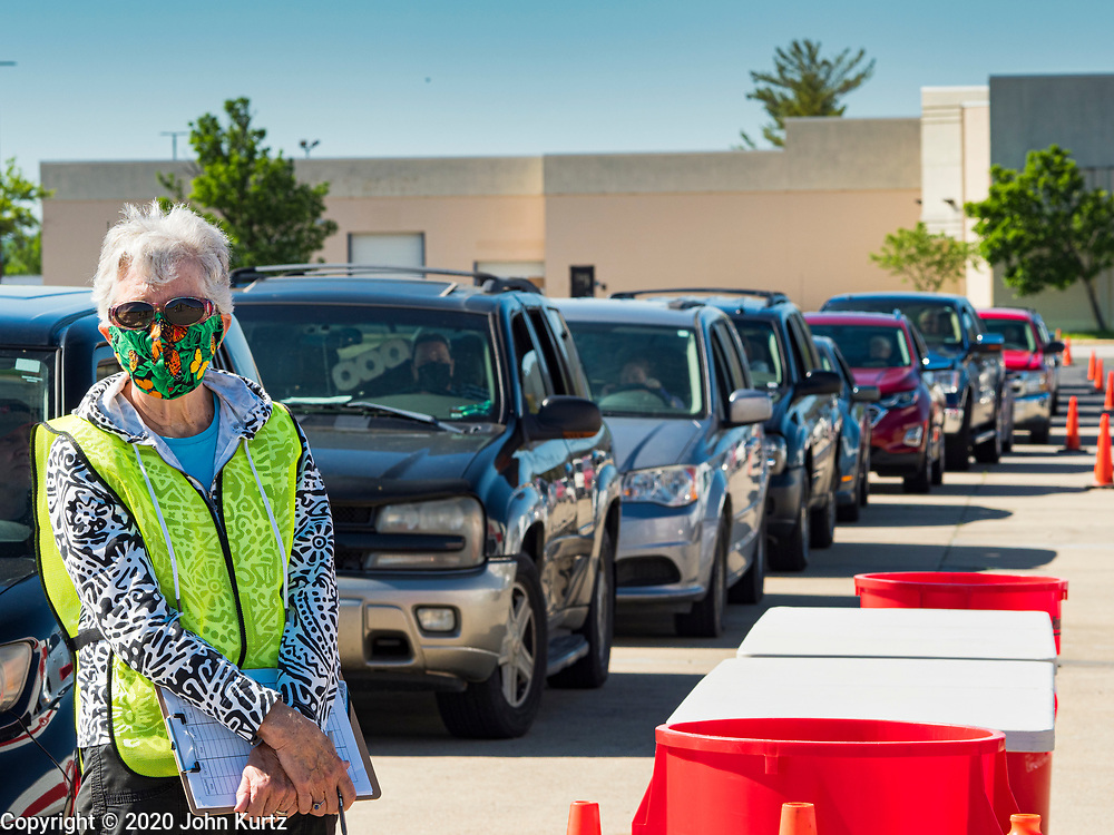 29 MAY 2020 - DES MOINES, IOWA: PHYLLIS JOHNSON waits to check people in at a produce distribution in a mall parking lot in Des Moines. The Des Moines Area Religious Council (DMARC) and Capitol City Fruit from Norwalk, IA, gave away 1,800 boxes of fresh produce with a mix of vegetables and fruit. The boxes contain enough produce to feed a family of four for a week. The produce was provided by the USDA Farmers to a Families food program. Because of the COVID-19 pandemic, the unemployment rate in Iowa hit 10.2% in May, the highest unemployment rate ever recorded in Iowa and food insecurity in Iowa is impacting communities throughout the state.          PHOTO BY JACK KURTZ