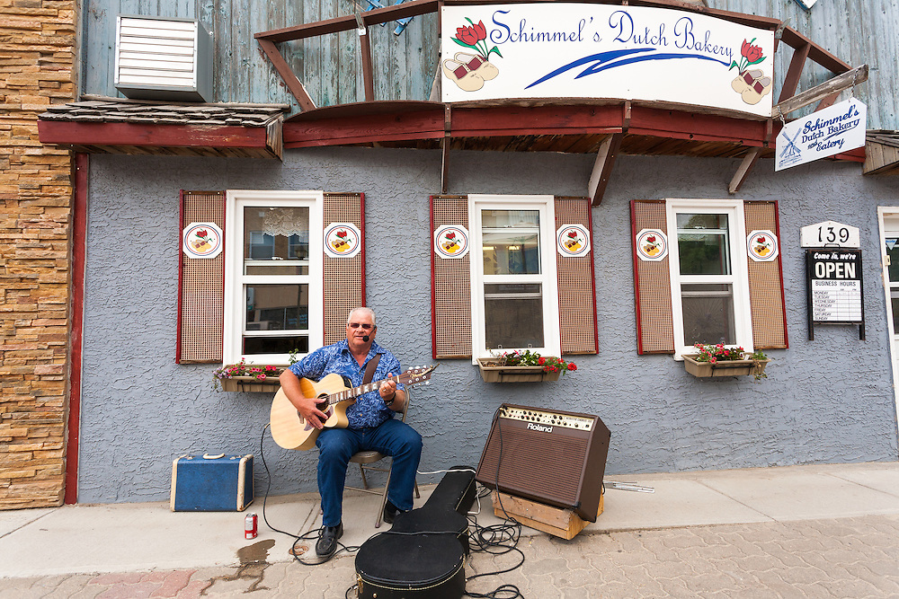 Larry Jaster, a local musician, performs in front of the bakery, owned by his friend (who asked him to come play guitar). Windscape Kite Festival, Swift Current, Saskatchewan.