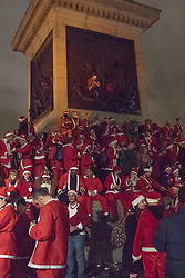 Trafalgar Square, London, December 12th 2015. SHigh spirits in Trafalgar Square as Santacon 2015 hits London. Every year in many cities around the world revellers dressed as Santa gather for pre-Christmas fun. PICTURED: A Santa sits on the knee of one of the people in the frieze on Nelson's column. ///FOR LICENCING CONTACT: paul@pauldaveycreative.co.uk TEL:+44 (0) 7966 016 296 or +44 (0) 20 8969 6875. ©2015 Paul R Davey. All rights reserved.