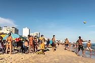 Rio de Janeiro, Brazil - March 9, 2019: The sun shines on a busy scene — football, bikinis, swimming — at the famous Ipanema Beach in Rio de Janeiro, Brazil.