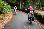 Een jongetje zit omgekeerd achterop de fiets