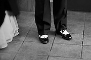 Feet of groom and his neat dress shoes, standing next to his bride, in the vestibule of their church following the wedding ceremony.