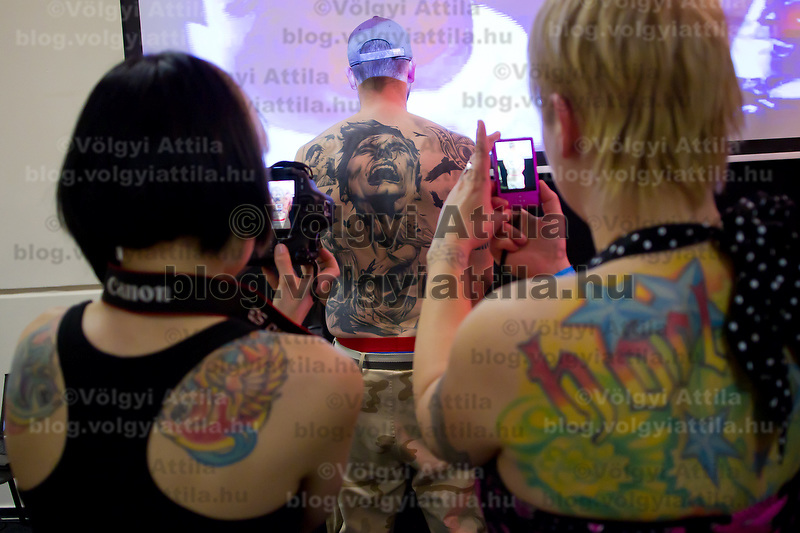 Participants take photos of tattoos on another during an international tattoo exhibition in Budapest, Hungary on February 26, 2012. ATTILA VOLGYI