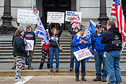 """Protesters hold signs during a """"Stop the Steal"""" rally in Harrisburg, Pennsylvania on January 5, 2021. Supporters of President Donald Trump urged legislators to decertify the election during the rally at the Pennsylvania State Capitol. (Photo by Paul Weaver)"""