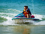 """13 FEBRUARY 2019 - SIHANOUKVILLE, CAMBODIA: Chinese tourists on Ocherteal Beach in Sihanoukville ride on personal watercraft that are being steered by Cambodian workers. There are about 80 Chinese casinos and resort hotels open in Sihanoukville and dozens more under construction. The casinos are changing the city, once a sleepy port on Southeast Asia's """"backpacker trail"""" into a booming city. The change is coming with a cost though. Many Cambodian residents of Sihanoukville  have lost their homes to make way for the casinos and the jobs are going to Chinese workers, brought in to build casinos and work in the casinos.      PHOTO BY JACK KURTZ"""