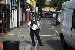 © London News Pictures. 30/08/2014. London, UK. Police at the scene of a fatal stabbing on Portobello Road in West London today (30/08/2014). A murder investigation has been launched after a Man aged in his fifties died of stab wounds in the early hours of this morning. Respect party politician George Galloway was alleged assaulted in the same area late yesterday evening. Photo credit : Ben Cawthra/LNP