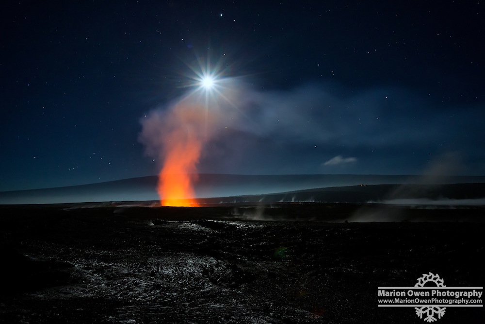 A full moon glows through a cloud forming over Halema'uma'u Crater in the Hawai'i Volcanoes National Park.