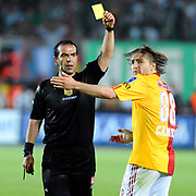 Referee's Bunyamin GEZER show the yellow card to Galatasaray's Caner ERKIN (R) during their Turkish Super League soccer match Galatasaray between Bursaspor at the AliSamiYen Stadium at Mecidiyekoy in Istanbul Turkey on Sunday 25 April 2010. Photo by TURKPIX