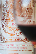 A glass of wine with the label of a bottle seen through the glass  - Chateau Baron Pichon Longueville, Pauillac, Medoc, Bordeaux, Grand Cru