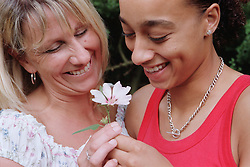 Portrait of lesbian couple standing together holding flower and laughing,
