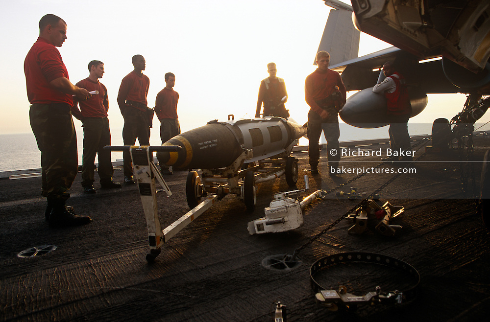 Red shirted ordnance men prepare and fit smart bombs to an F/A-18 fighter jet on deck of USS Harry S Truman. The Truman is the largest and newest of the US Navy's fleet of new generation carriers, a 97,000 ton floating city with a crew of 5,137, 650 are women.
