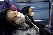 Asian man hanging halve out of his seat during a commuting nap Japan
