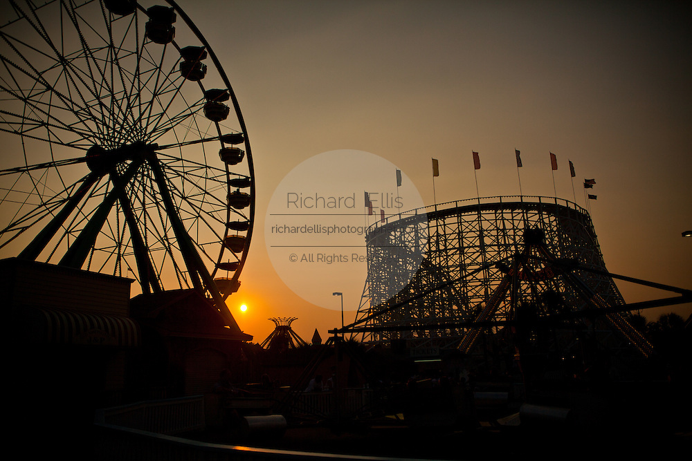 The Ferris Wheel and roller coaster is silhouetted during Sunset at Family Kingdom amusement park along the beachfront in Myrtle Beach, SC.