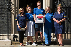 London, UK. 20th July, 2021. Matthew Tovey (c) and other NHS workers from the grassroots NHSPay15 campaign pose outside 10 Downing Street before presenting a petition signed by over 800,000 people calling for a 15% pay rise for NHS workers. At the time of presentation of the petition, the government was believed to be preparing to offer NHS workers a 3% pay rise in 'recognition of the unique impact of the pandemic on the NHS'.