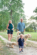 A family with their dogs walks along a path at World's End park in Hingham, Massachusetts, September, 2018.