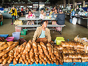 16 JUNE 2016 - PAKSE, CHAMPASAK, LAOS:  A woman sells baguettes in Dao Heuang Market, the largest market in Pakse. Lao, Cambodians and Vietnamese eat lots of baguettes, a legacy of French colonialism. Pakse is the capital of Champasak province in southern Laos. It sits at the confluence of the Xe Don and Mekong Rivers. It's the gateway city to 4,000 Islands, near the border of Cambodia and the coffee growing highlands of southern Laos.     PHOTO BY JACK KURTZ