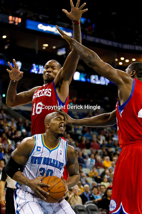 January 3, 2011; New Orleans, LA, USA; New Orleans Hornets power forward David West (30) is hit in the face and fouled by Philadelphia 76ers power forward Elton Brand (42) as center Marreese Speights (16) defends on the play during the third quarter at the New Orleans Arena.   Mandatory Credit: Derick E. Hingle