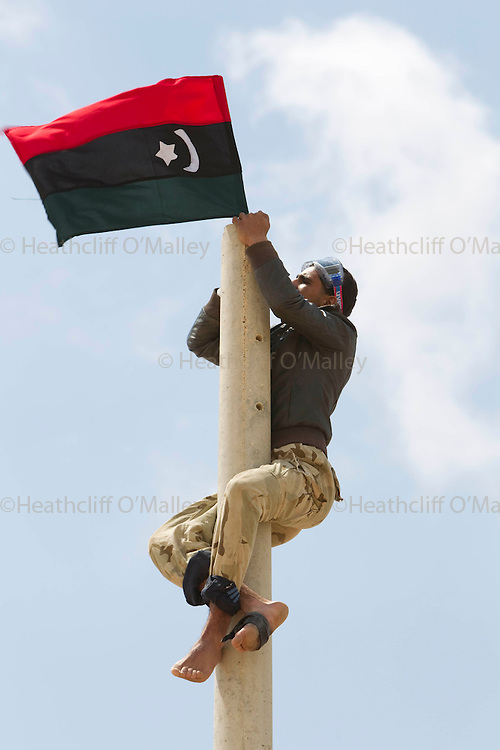 Mcc0030300 . Daily Telegraph..A Rebel fighter shimmy place their flag on a lamp post on the road to Brega about 50kms from Ajdabiyah. Brega is still in the control of Gaddafi's army and the rebels seem to be gaining little ground...Brega 3 April 2011