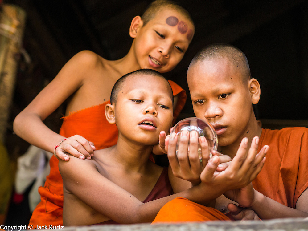 """02 JULY 2013 - ANGKOR WAT, SIEM REAP, SIEM REAP, CAMBODIA:  Buddhist novices at a small monastery near the Bayon temple in the Angkor Wat complex. The dots, which look like bruises, on the novice in the background, are from """"cupping therapy."""" Angkor Wat is the largest temple complex in the world. The temple was built by the Khmer King Suryavarman II in the early 12th century in Yasodharapura (present-day Angkor), the capital of the Khmer Empire, as his state temple and eventual mausoleum. Angkor Wat was dedicated to Vishnu. It is the best-preserved temple at the site, and has remained a religious centre since its foundation– first Hindu, then Buddhist. The temple is at the top of the high classical style of Khmer architecture. It is a symbol of Cambodia, appearing on the national flag, and it is the country's prime attraction for visitors. The temple is admired for the architecture, the extensive bas-reliefs, and for the numerous devatas adorning its walls. The modern name, Angkor Wat, means """"Temple City"""" or """"City of Temples"""" in Khmer; Angkor, meaning """"city"""" or """"capital city"""", is a vernacular form of the word nokor, which comes from the Sanskrit word nagara. Wat is the Khmer word for """"temple grounds"""", derived from the Pali word """"vatta."""" Prior to this time the temple was known as Preah Pisnulok, after the posthumous title of its founder. It is also the name of complex of temples, which includes Bayon and Preah Khan, in the vicinity. It is by far the most visited tourist attraction in Cambodia. More than half of all tourists to Cambodia visit Angkor.         PHOTO BY JACK KURTZ"""