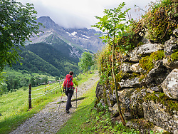 Woman hiking in the High Pyrenees on a single trail with view over Cirque de Gavarnie, France